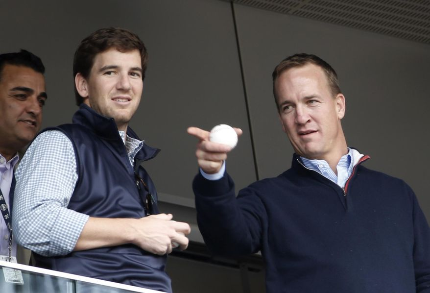 Denver Broncos quarterback Peyton Manning, right, points out something in the stadium to his brother, New York Giants quarterback Eli Manning, from New York Yankees' Derek Jeter's suite during a baseball game between the Yankees and the Tampa Bay Rays at Yankee Stadium in New York, Sunday, May 4, 2014. (AP Photo/Kathy Willens)