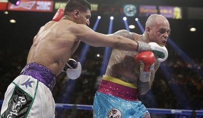 England's Amir Khan, left, lands a right against Luis Collazo in their silver welterweight title boxing fight Saturday, May 3, 2014, in Las Vegas. (AP Photo/Isaac Brekken)