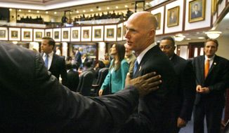 FILE - In a Friday, May 2, 2014 file photo, Florida Governor Rick Scott visits members of the Florida House, on the last day of the 2014 Legislative session in Tallahassee. He congratulated Rep. Jeanette M. Nunez, R- Miami, Senator Jack Latvala, R- Clearwater, on the passage of an immigrant tuition bill during the session. Scott largely succeeded with many of his session goals. (AP Photo/The Tampa Bay Times, Scott Keeler, File)