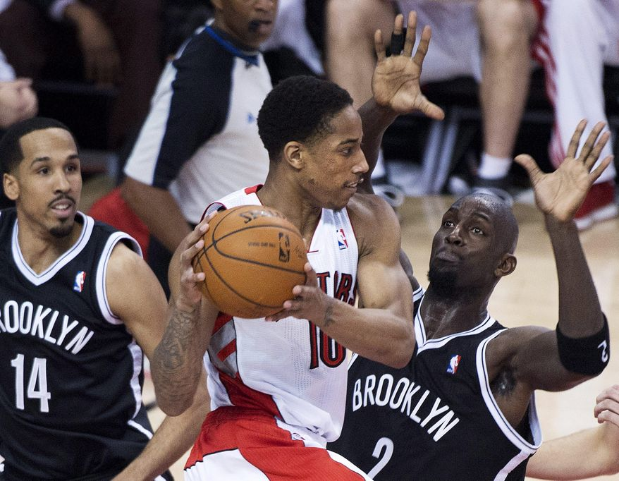 Toronto Raptors guard DeMar DeRozan, center, looks for a pass against Brooklyn Nets forward Kevin Garnett (2) and Shaun Livingston (14) during the first half of Game 7 of the opening-round NBA basketball playoff series in Toronto, Sunday, May 4, 2014. (AP Photo/The Canadian Press, Nathan Denette)