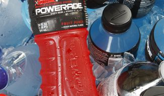 FILE - In this Aug. 5, 2010 file photo, bottles of Powerade sports drink and other Coca-Cola products are chilled over ice in Orlando, Fla. A controversial ingredient, brominated vegetable oil, is being removed from some Powerade sports drinks. (AP Photo/Jon Elswick, File)