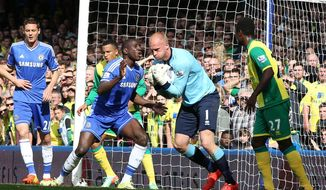 Chelsea's Demba Ba, center left, reacts as Norwich City's goalkeeper John Ruddy collects the ball after a header from Chelsea's John Terry during their English Premier League soccer match at Stamford Bridge stadium in London Sunday May 4, 2014. (AP Photo/Alastair Grant)