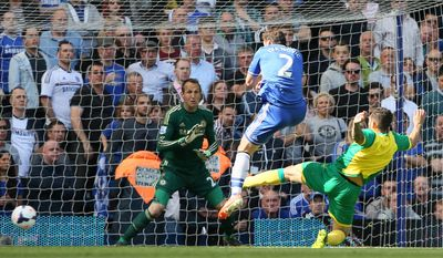 Chelsea's Branislav Ivanovic, center, defends as Norwich's Bradley Johnson misses the ball watched by Chelsea's goalkeeper Mark Schwarzer during their English Premier League soccer match at Stamford Bridge stadium in London Sunday May 4, 2014. (AP Photo/Alastair Grant)