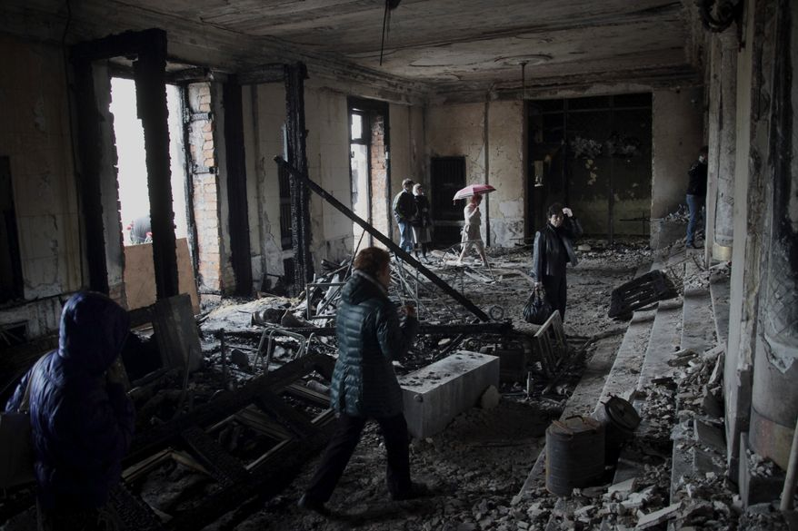 People walk inside the burnt trade union building in Odessa, Ukraine, Sunday, May 4, 2014. More than 40 people died in the riots, which some from gunshot wounds, but most in a horrific fire that tore through the trade union building late Friday. (AP Photo/Sergei Poliakov)