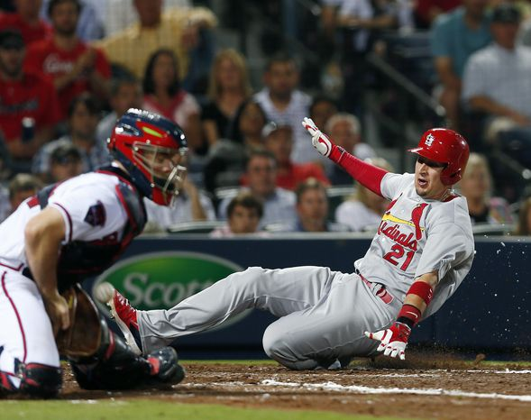 St. Louis Cardinals right fielder Allen Craig (21) scores on a Peter Bourjos (8) base hit as Atlanta Braves catcher Evan Gattis (24) handles the late throw in the sixth inning of a baseball game Monday, May 5, 2014 in Atlanta.  (AP Photo/John Bazemore)