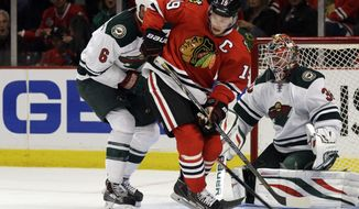 Chicago Blackhawks' Jonathan Toews (19) battles for the puck against Minnesota Wild's Marco Scandella (6) as goalie Ilya Bryzgalov (30) looks on during the second period in Game 2 of an NHL hockey second-round playoff series in Chicago, Sunday, May 4, 2014. The Blackhawks won 4-1. (AP Photo/Nam Y. Huh)