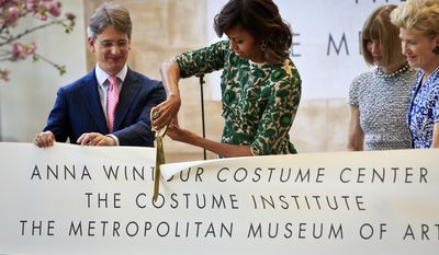 Vogue editor Anna Wintour, second from right, Metropolitan Museum director Thomas Campbell, left, and museum president Emily Rafferty, right, looks on as first lady Michelle Obama cuts the ribbon at a dedication ceremony for the Anna Wintour Costume Center, Monday May 5, 2014, at the Metropolitan Museum of Art in New York. (AP Photo/Bebeto Matthews)