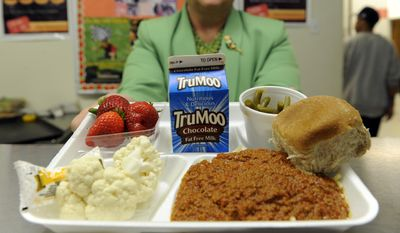 Becky Domokos-Bays, the Director of Food and Nutrition Services at Alexandria City Public Schools, holds up a tray of food during lunch service at the Patrick Henry Elementary School in Alexandria, Va., Tuesday, April 29, 2014. (AP Photo/Susan Walsh)