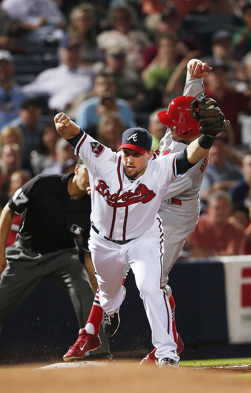 St. Louis Cardinals Peter Bourjos (8) is forced out at third base by Atlanta Braves third baseman Chris Johnson as he tries to advance on a Yadier Molina  base hit in the sixth inning of a baseball game Monday, May 5, 2014, in Atlanta.  (AP Photo/John Bazemore)