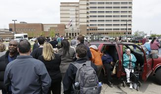 People stand outside a Veterans Affairs hospital after they were evacuated, Monday, May 5, 2014, in Dayton, Ohio. A city official says a suspect is in police custody after a shooting at the Veterans Affairs hospital in Ohio that left one person with a minor injury. (AP Photo/Al Behrman)