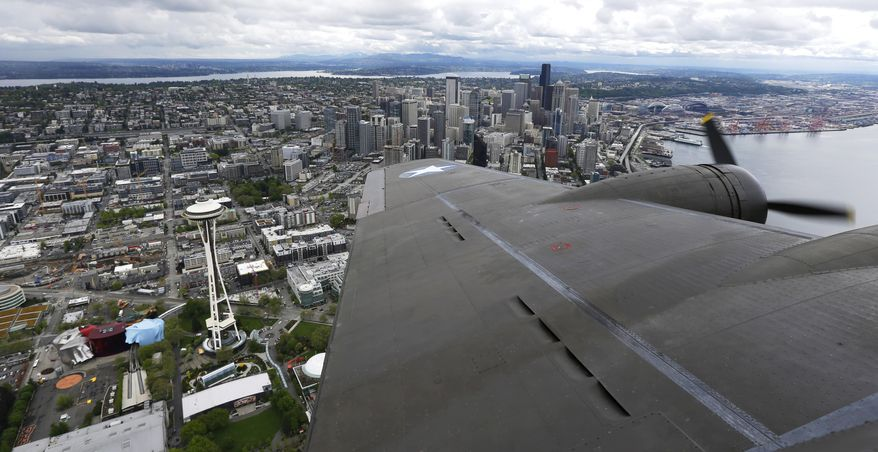 """The Space Needle and downtown Seattle are viewed over the wing of a Boeing B-17 """"Flying Fortress"""" bomber Monday, May 5, 2014, as it flies over Seattle. The recreated model of the """"Memphis Belle"""" World War II airplane will be available for paid rides and donation-based ground tours on May 10-11, 2014 at the Renton Municipal Airport in Renton, Wash. (AP Photo/Ted S. Warren)"""