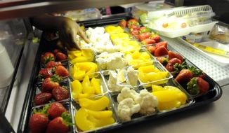 Fruit and vegetables are served during lunch service at the Patrick Henry Elementary School in Alexandria, Va., Tuesday, April 29, 2014. (AP Photo/Susan Walsh)