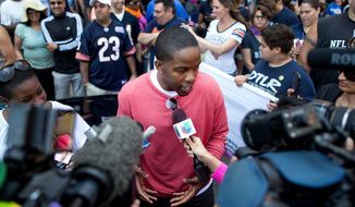 FILE - In this June 30, 2013 file photo, former NFL football player Wade Davis, grand marshal for the Chicago Gay Pride Parade, speaks to reporters prior to the parade in Chicago. One of the people enlisted to help advise All-American defensive end Michael Sam of Missouri before publicly announcing he was gay was Davis, a former NFL player who came out in 2012 - nine years after retiring. (AP Photo/Scott Eisen)