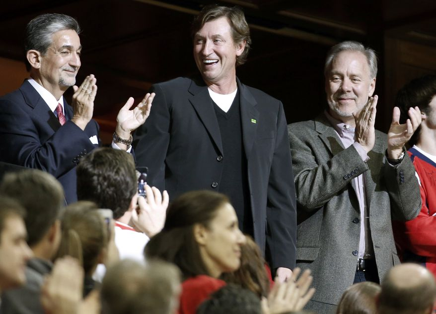 Ted Leonsis, left, owner of the Washington Capitals, stands and applauds Wayne Gretzky, center, as Gretzky is announced in the third period of an NHL hockey game against the Montreal Canadiens, Friday, Nov. 22, 2013, in Washington. The Canadiens won 3-2. (AP Photo/Alex Brandon)