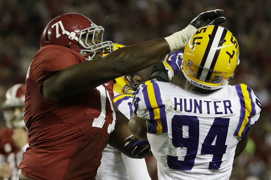 Alabama offensive linesman Cyrus Kouandjio (71) blocks LSU defensive end Danielle Hunter (94) in the first half of an NCAA college football game in Tuscaloosa, Ala., Saturday, Nov. 9, 2013.  (AP Photo/Dave Martin)
