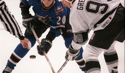 Washington Capitals' Michal Pivonka (20) fights for the puck against Los Angeles Kings' Wayne Gretzky (99) during a faceoff in the first period of the game at the Forum in Inglewood, Calif.  Thursday, Nov. 30, 1995. (AP Photo/Damian Dovarganes)