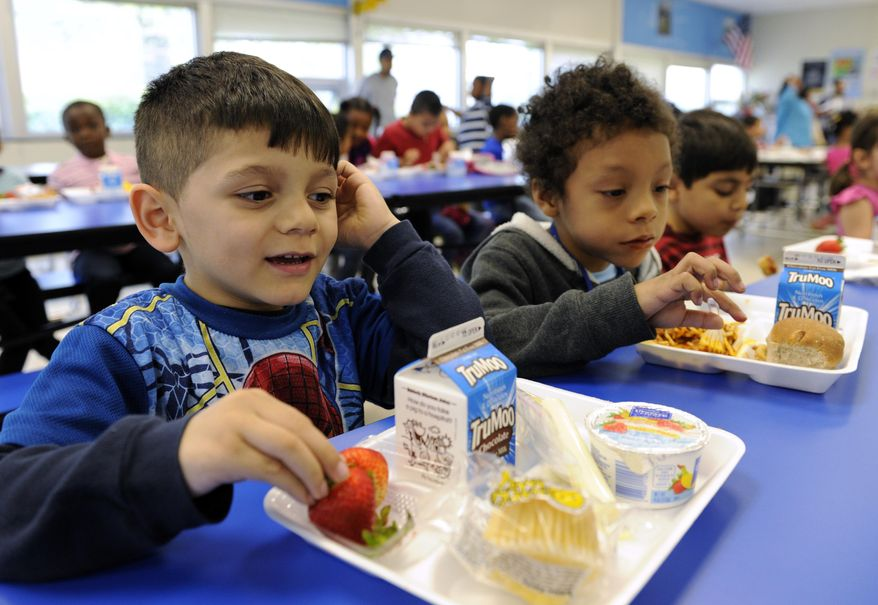 In this Tuesday, April 29, 2014 photo, Biden Arias-Romers, 5, left, and Nathaniel Cossio-Boatwright, 6, eat lunch at the Patrick Henry Elementary School in Alexandria, Va. Starting next school year, pasta and other grain products in schools will have to be whole-grain rich, or more than half whole grain. The requirement is part of a government effort to make school lunches and breakfasts healthier. (AP Photo/Susan Walsh)