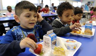 Biden Arias-Romers, 5, left, and Nathaniel Cossio-Boatwright, 6, right, eat lunch at the Patrick Henry Elementary School in Alexandria, Va., Tuesday, April 29, 2014. (AP Photo/Susan Walsh)