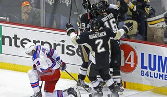 Pittsburgh Penguins' Jussi Jokinen, center not shown, celebrates his goal with teammates as New York Rangers' Marc Staal (18) kneels on the ice in the third period of game 2 of a second-round NHL playoff hockey series against the New York Rangers in Pittsburgh Sunday, May 4, 2014. The Penguins won 3-0, to tie the series at 1-1. (AP Photo/Gene J. Puskar)