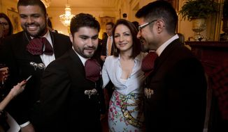 Singer Gloria Estefan, center, from Miami, with members of Mariachi band, Los Gallos Negros, at a celebration of Cinco de Mayo in the East Room of the White House in Washington, Monday, May 5, 2014. (AP Photo/Pablo Martinez Monsivais)