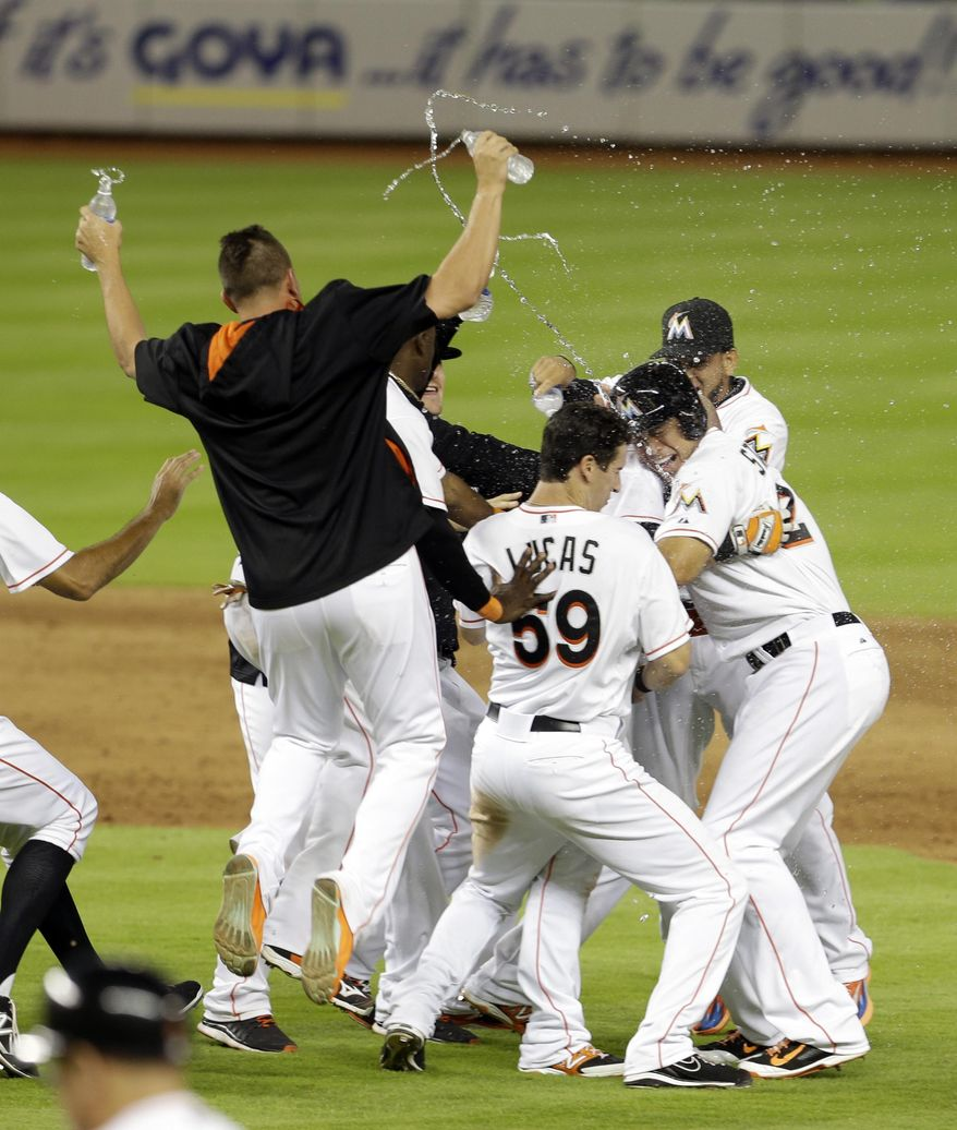 Miami Marlins players jump on Casey McGehee as they celebrate their 4-3 win against the New York Mets during the ninth inning of a baseball game in Miami, Monday, May 5, 2014. McGehee hit the game wining single driving in Christian Yelich. (AP Photo/Alan Diaz)