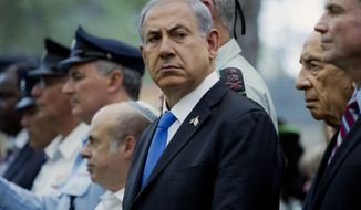 Israeli Prime Minister Benjamin Netanyahu, center, stands next to President Shimon Peres, second right, as they commemorate Memorial Day for fallen soldiers and victims of terrorism in a ceremony on Mt. Herzl military cemetery in Jerusalem on Monday, May 5, 2014. Israel came to a standstill on Monday as sirens wailed across the country on its annual Memorial Day. (AP Photo/Jim Hollander, Pool)