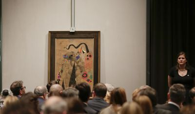 A painting by Joan Miro hangs on the turn table for bidding during an impressionist and modern art auction at Christie's, Tuesday, May 6, 2014, in New York. The auction house says it expects to raise over $245 million from the sale of works including those by Monet, Renoir, Picasso, Degas, Matisse and Kandinsky. (AP Photo/Julie Jacobson)