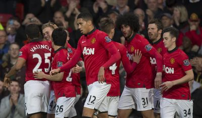 Manchester United's James Wilson, second left, celebrates with teammates after scoring past Hull City's goalkeeper Eldin Jakupovic during their English Premier League soccer match at Old Trafford Stadium, Manchester, England, Tuesday May 6, 2014. (AP Photo/Jon Super)