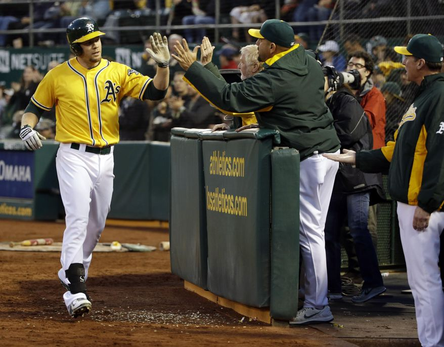 Oakland Athletics' Brandon Moss is greeted in the dugout after his two-run home run against the Seattle Mariners during the fourth inning of a baseball game on Monday, May 5, 2014, in Oakland, Calif. (AP Photo/Marcio Jose Sanchez)