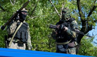 The pro-Russian gunmen surrounded a military base in Donetsk, Ukraine, Tuesday and said they were holding negotiations with commanders inside to ensure that they did not join forces with government-allied groups. (ASSOCIATED PRESS PHOTOGRAPHS)