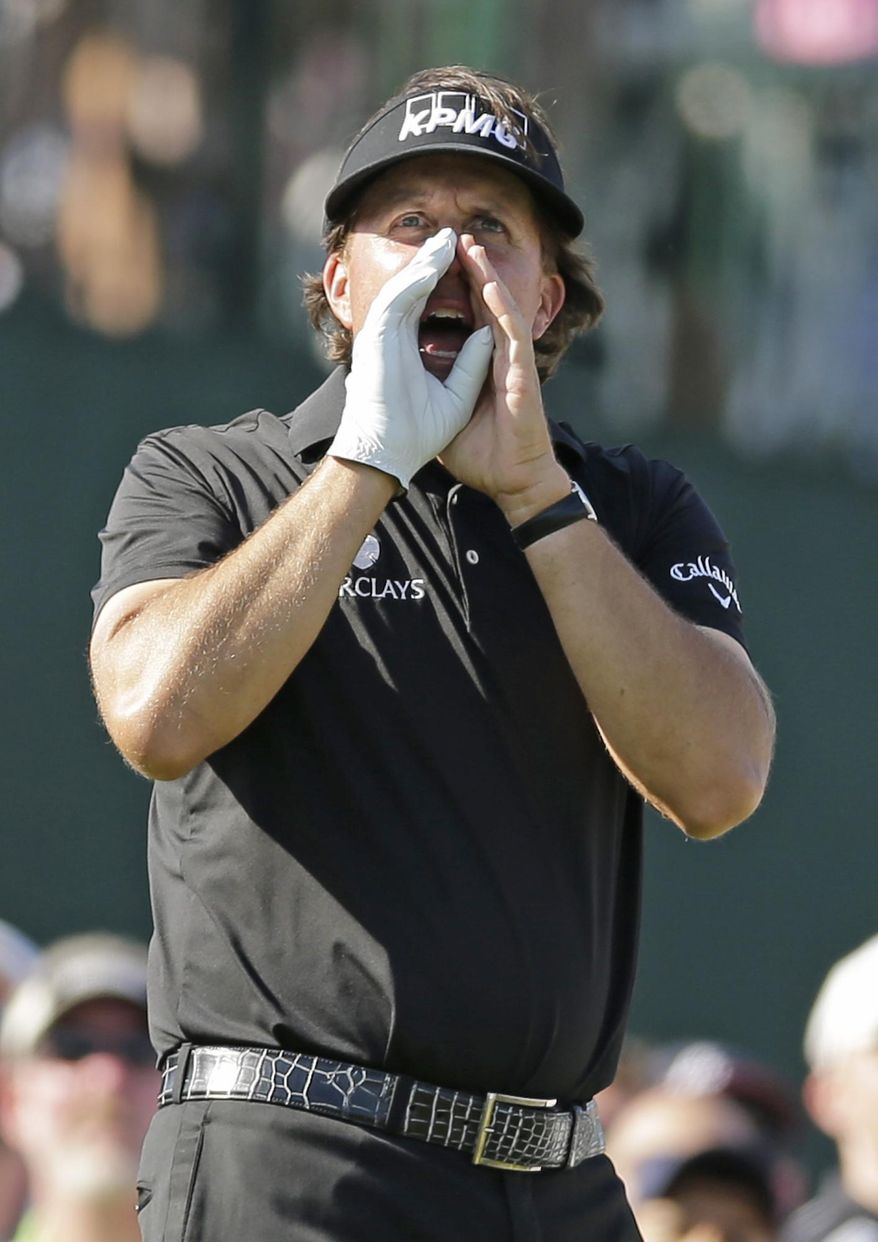 Phil Mickelson shouts to fans after hitting his drive right on the 17th hole during the final round of the Wells Fargo Championship golf tournament in Charlotte, N.C., Sunday, May 4, 2014. (AP Photo/Chuck Burton)