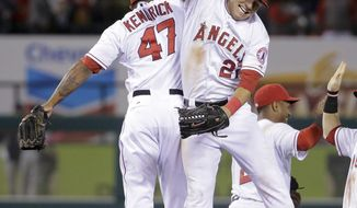 Los Angeles Angels second baseman Howie Kendrick, left, and center fielder Mike Trout celebrate their win against the New York Yankees during a baseball game in Anaheim, Calif., Monday, May 5, 2014. (AP Photo/Chris Carlson)
