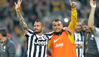 Juventus players Simone Pepe, left, and Arturo Vidal celebrate at the end of a Serie A soccer match againsts Atalanta, at the Juventus stadium, in Turin, Italy, Monday, May 6, 2014. Juventus clinched its third straight and 30th overall Serie A title. (AP Photo/Massimo Pinca)
