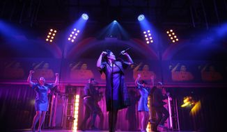 "This image released by The O and M Co. shows Ruthie Ann Miles as Imelda Marcos, center, in ""Here Lies Love,"" with concept and lyrics by David Byrne, music by David Byrne and Fatboy Slim, at The Public Theater in New York. (AP Photo/The O and M Co., Joan Marcus)"