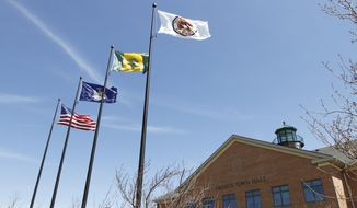 Flags fly over Greece Town Hall in Greece, N.Y., Monday, May 5, 2014. The Supreme Court upheld prayers being allowed before Greece Town Board meetings. (AP Photo/The Rochester Democrat and Chronicle, Shawn Dowd)