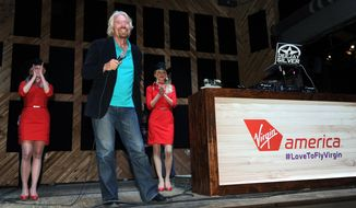 """In this Monday, May 5, 2014 photo released by Virgin America Airlines, Virgin Group Founder Sir Richard Branson is joined by Virgin America teammates during an informal """"Virgin-style rally' with local friends, city leaders and teammates to build support to secure two gates at Love Field, near downtown Dallas.Branson said Tuesday that Virgin should get the gates at Love Field to create competition for Southwest Airlines, which controls most of the gates there. The U.S. Justice Department agrees. (AP Photo/Virgin America, Bob Riha, Jr.)"""