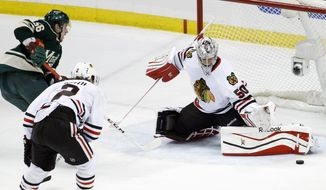 Chicago Blackhawks goalie Corey Crawford (50) deflects a shot by Minnesota Wild left wing Erik Haula (56), of Finland, in front of Blackhawks defenseman Duncan Keith (2) during the first period of Game 3 of an NHL hockey second-round playoff series in St. Paul, Minn., Tuesday, May 6, 2014. (AP Photo/Ann Heisenfelt)