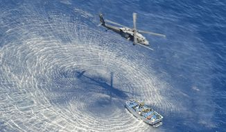 In this  May 5, 2014 photo provided by the U.S. Air Force, a U.S. Air Force HH-60G Pavehawk helicopter from the 55th Rescue Squadron hovers 600 nautical miles off the Pacific Coast of Mexico to hoist two badly burned Chinese fishermen. The two were among 17 Chinese crew members believed aboard a fishing vessel that caught fire and sank in the Pacific Ocean. Two died from burn injuries, seven were determined to be in good condition and six are believed missing, said Maj. Sarah Schwennesen of Davis-Monthan Air Force Base in Tucson, Ariz. (AP Photo/U.S. Air Force, Staff Sgt. Adam Grant)