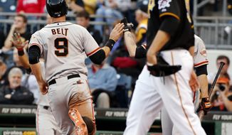 San Francisco Giants' Brandon Belt (9) scores on a sacrifice fly to center by Giants' Ehire Adrianza as Pittsburgh Pirates starting pitcher Charlie Morton, right, walks back to the mound during the second inning of a baseball game in Pittsburgh, Tuesday, May 6, 2014. (AP Photo/Gene J. Puskar)