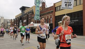 FILE - In this May 21, 2011 file photo provided by the Department of Defense, Maj. George Kraehe, of Albequerque, N.M., center,  and other runners pass the Fargo Theater during a marathon in Fargo, N.D. The Fargo Marathon, being run Saturday, May, 10, 2014, is celebrating its 10th anniversary this year with more than 23,000 participants. (AP Photo/Department of Defense, Senior Master Sgt. David H. Lipp, File)