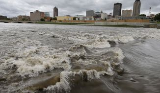 """** FILE ** In this May 30, 2013, file photo, water splashes over the Center Street Dam in the swollen Des Moines River in downtown Des Moines, Iowa. Climate change's assorted harms """"are expected to become increasingly disruptive across the nation throughout this century and beyond,"""" the National Climate Assessment concluded Tuesday. (AP Photo/Charlie Neibergall, File)"""