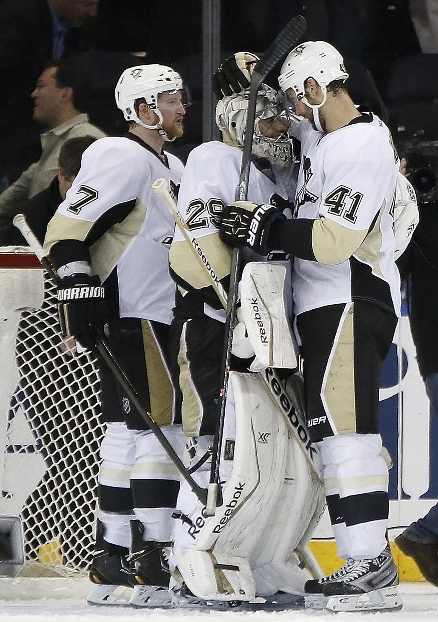 Pittsburgh Penguins defensemen Paul Martin, (7) left, and Robert Bortuzzo (41) celebrate with Penguins goalie Marc-Andre Fleury (29) after the Penguins shut out the New York Rangers 2-0 in their second-round NHL Stanley Cup hockey playoff game at Madison Square Garden in New York, Monday, May 5, 2014.  The Penguins take a 2-1 lead in the series. (AP Photo/Kathy Willens)