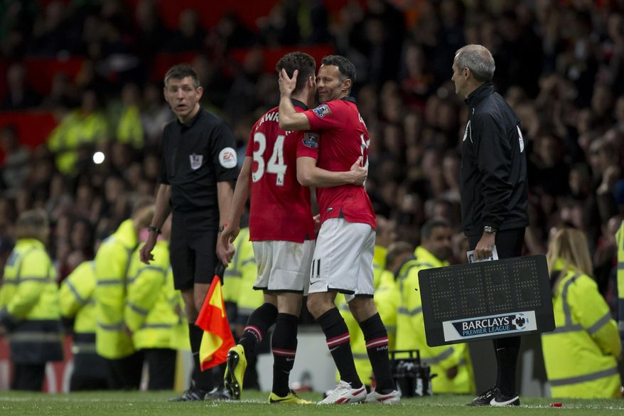 Manchester United's interim manager Ryan Giggs, right, embraces teammate Tom Lawrence as he takes to the pitch as a substitute during his team's English Premier League soccer match against Hull at Old Trafford Stadium, Manchester, England, Tuesday May 6, 2014. (AP Photo/Jon Super)