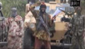 In this image made from video received by The Associated Press on Monday, May 5, 2014, Abubakar Shekau, the leader of Nigeria's Islamic extremist group Boko Haram, speaks in a video in which his group claimed responsibility for the April 15 mass abduction of nearly 300 teenage schoolgirls in northeast Nigeria. Shekau threatened to sell the nearly 300 teenage schoolgirls abducted from a school in the remote northeast three weeks ago, in a new videotape received Monday. It was unclear if the video was made before or after reports emerged last week that some of the girls have been forced to marry their abductors — who paid a nominal bride price of $12 — and that others have been carried into neighboring Cameroon and Chad. Those reports could not be verified. (AP Photo)
