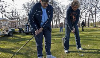 "In this April 15, 2014 photo, golf instructor Laura Carle, left, demonstrates the correct way to strike the ball while chipping to student Suzy Neally during a ""boot camp"" for women at the Carthage Golf Club in Carthage, Ill. Tuesday night sessions teach some golf basics, like putting and chipping, and pair new golfers with more seasoned veterans of the nine-hole public course. (AP Photo/Quincy Herald-Whig, Phil Carlson)"