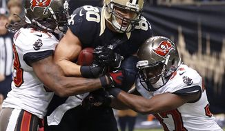 FILE - In this Sunday, Dec. 29, 2013, file photo, New Orleans Saints tight end Jimmy Graham (80) pulls in a touchdown reception between Tampa Bay Buccaneers free safety Keith Tandy (37) and free safety Dashon Goldson, left, in the first half of an NFL football game, in New Orleans. The NFL Players Association confirmed Wednesday, May 7, 2014, that it filed a grievance on behalf of Graham concerning the Saints tight end's franchise tag designation. At issue is whether the NFL was correct to apply the tight end tag to Graham or whether Graham should have received the more lucrative wide receiver tag, a difference of $5 million. (AP Photo/Bill Haber, File)