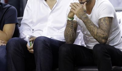 Former soccer player David Beckham, right, of England, sits with Bolivian businessman Marcelo Claure, during Game 1 of an NBA basketball Eastern Conference semifinal playoff series between the Miami Heat and Brooklyn Nets, Tuesday, May 6, 2014, in Miami. (AP Photo/Lynne Sladky)