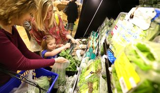 Ella Hilborn, 4, grabs spinach while her mom Jessica Hilborn, right, and grandmother Ruth Graper, help while shopping at the Dubuque Food Co-op on May 5, 2014, in Dubuque, Iowa.  Up to 500 members attend the opening of the Dubuque Food Co-op, marking a milestone years in the making to create a market that focuses on local food.  (AP Photo/The Telegraph Herald, Jessica Reilly)