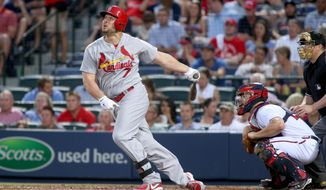 St. Louis Cardinals' Matt Holliday (7) follows through on a single to left center scoring Cardinals' Adam Wainwright and Matt Carpenter as Atlanta Braves catcher Evan Gattis, right, is shown in the fourth inning of a baseball game, Wednesday May 7, 2014, in Atlanta. (AP Photo/Jason Getz)