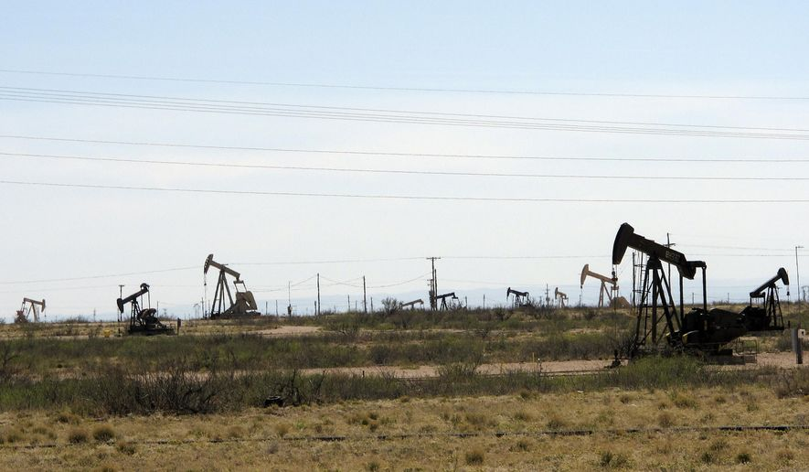 This April 9, 2014, photo shows oil rigs in the Loco Hills field in Eddy County, near Artesia, New Mexico, one of the most active regions of the Permian Basin. (AP Photo/Jeri Clausing)